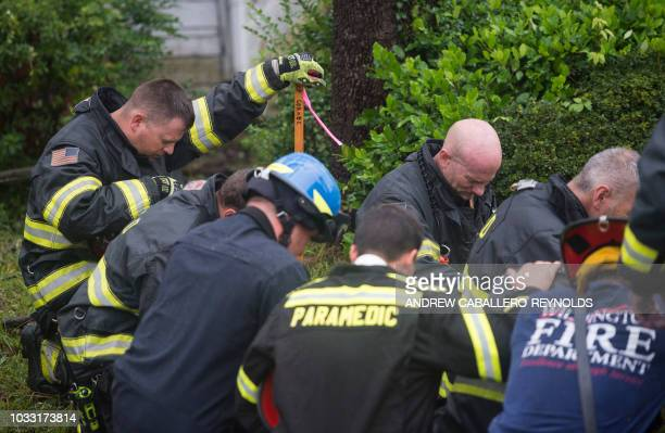 TOPSHOT Firefighters pray during an operation to remove a tree that fell on a house and killed two residents as Hurricane Florence made landfall in...