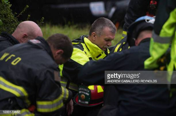 Firefighters pray during an operation to remove a tree that fell on a house and killed two residents as Hurricane Florence made landfall in...