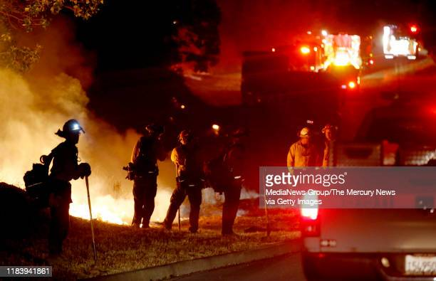 Firefighters prepare to cut a break as they battle the Kincade Fire along Mayacama Club Drive on the outskirts of Santa Rosa Calif on Monday Oct 28...