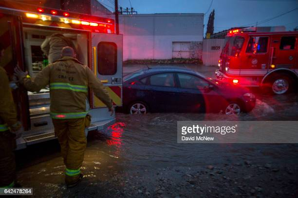 Firefighters prepare to transport a patient by ambulance at the scene of a car stuck in flooding as a powerful storm moves across Southern California...