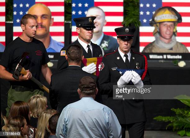 Firefighters present American flags Arizona flags and pulaskis to family member of the fallen firefighters during a memorial service honoring 19...