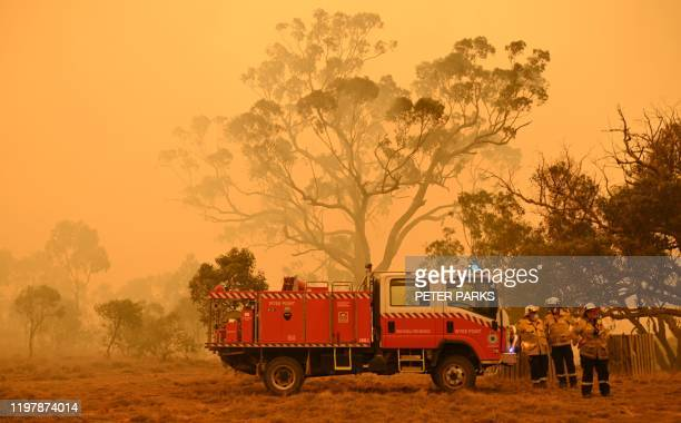 Firefighters protect a property from bushfires burning near the town of Bumbalong south of Canberra on February 1, 2020. - Authorities in Canberra on...