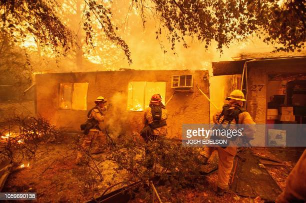 Firefighters push down a wall while battling against a burning apartment complex in Paradise, north of Sacramento, California on November 09, 2018. -...