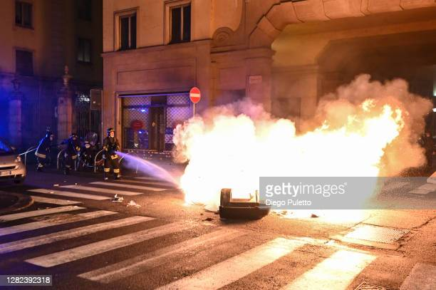 Firefighters put out a fire as protesters gather during an anti government demonstration on October 26 2020 in Turin Italy Following a surge in new...