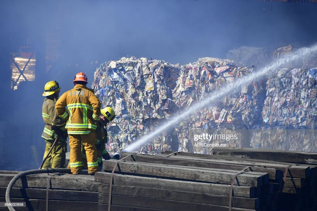 Firefighters put out a fire at a paper recycling facility south of the downtown area in Los Angeles, California on October 5, 2017. /