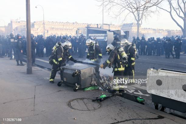 Firefighters put out a fire in a burning trash bin during a Yellow vest antigovernment demonstration on February 16 2019 in Paris on Esplanade des...