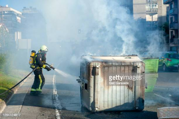 Firefighters put out fire from a burning container during protests by Basque anti-fascists against Spanish far-right party, Vox rally on July 03,...