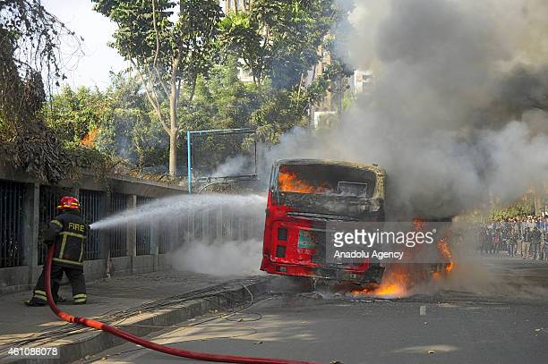 Firefighters put out fires after bus and car are set on fire during incidents of political violence in Bangladesh's capital Dhaka on January 6 2015...
