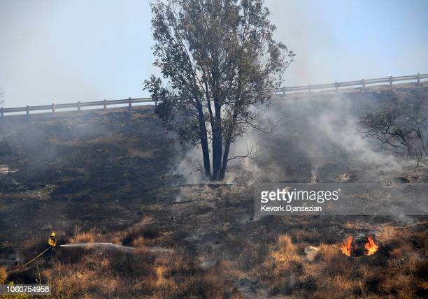 Firefighters put out hotspots as the Peak Fire burns in the hills behind homes on November 12 2018 in Simi Valley California Multiple fires are...