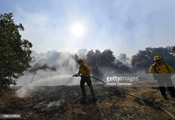 Firefighters put out hotspots as they battle the Peak Fire on November 12 2018 in Simi Valley California Multiple fires are burning throughout the...