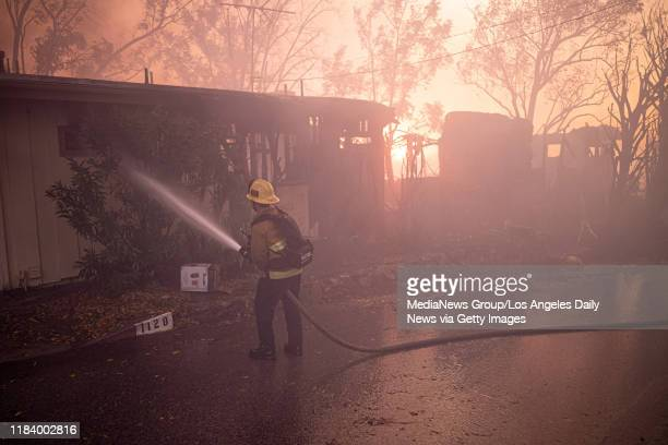 Firefighters put water on a burning home along Tigertail Rd in Los Angeles in the Getty fire Monday October 28 2019
