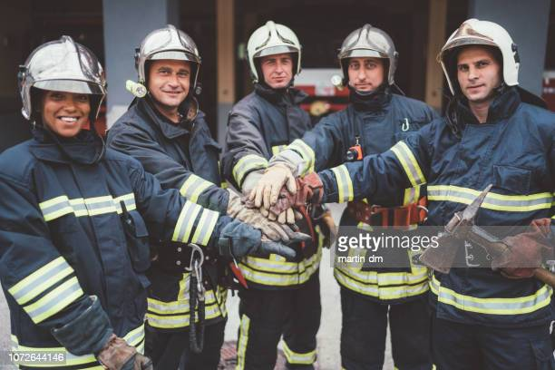 firefighters putting hands together - fire protection suit stock photos and pictures