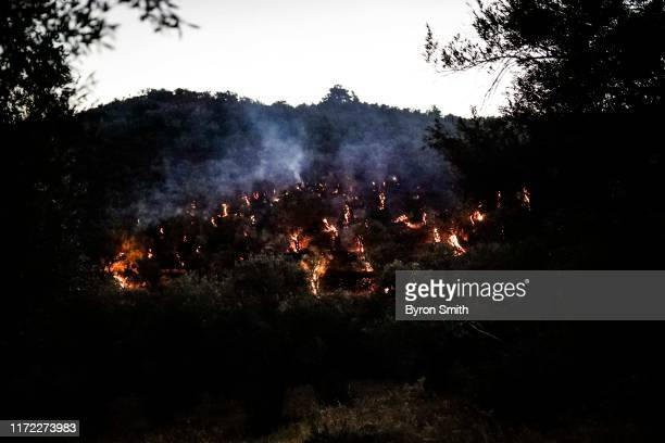 Firefighters race to put out brush-fires on nearby hills on the outskirts of a refugee camp on September 29, 2019 of Moria, Greece. At least one...