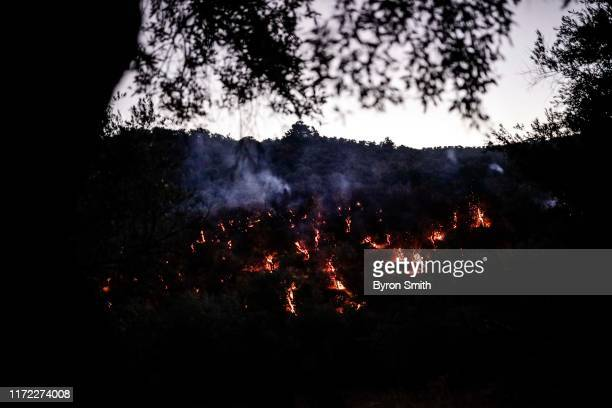 Firefighters race to put out brushfires on nearby hills on the outskirts of a refugee camp on September 29 2019 of Moria Greece At least one infant...