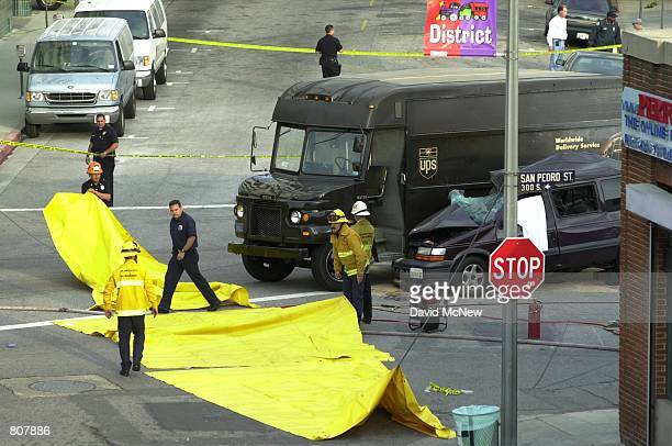 Firefighters raise tarps to hide a corpse in a minivan May 2 2001 in Los Angeles CA following the crash of a Metropolitan Transit Authority bus that...