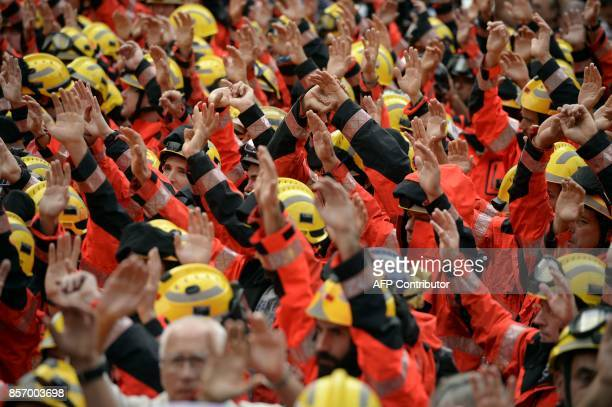 Firefighters raise their hands during a general strike in Barcelona called by Catalan unions on October 3 2017 Large numbers of Catalans are expected...