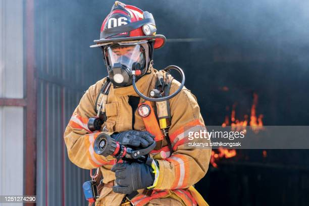 firefighters ready to spray water. - defending stock pictures, royalty-free photos & images