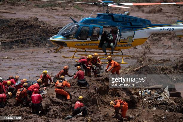TOPSHOT Firefighters receive equipment to open a vehicle found in the mud as they search for victims of Friday's dam collapse at an ironore mine...