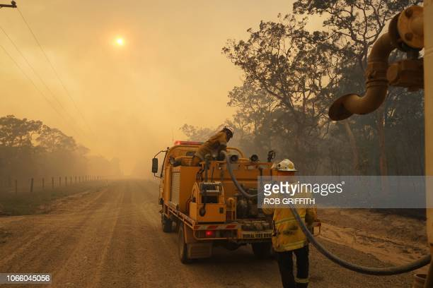 TOPSHOT Firefighters refill their water from a water tanker in Pacific Drive in Deepwater National Park area of Queensland on November 28 2018...