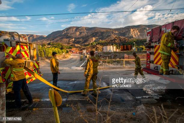 Firefighters refill their water tank on their way to control hotspots of the Maria Fire in Santa Paula Ventura County California on November 02 2019