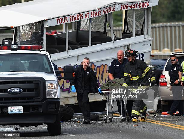 Firefighters remove a body from the scene of a crash between a tour bus and a tourist duck boat on the Aurora Bridge in Seattle Washington on...