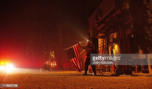 Firefighters remove a US flag from a property as flames race into the area during the Kincade fire in Healdsburg California on October 27 2019...