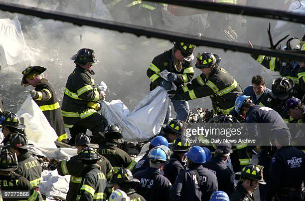 Firefighters remove body of victim from the smoldering remains of American Airlines flight 587 after it crashed in the Rockaway section of Queens