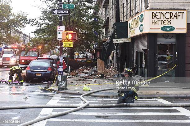 Firefighters remove hoses from 13 Avenue in front of burned out storefront Fire companies NYPD Red Cross and other emergency response personnel...