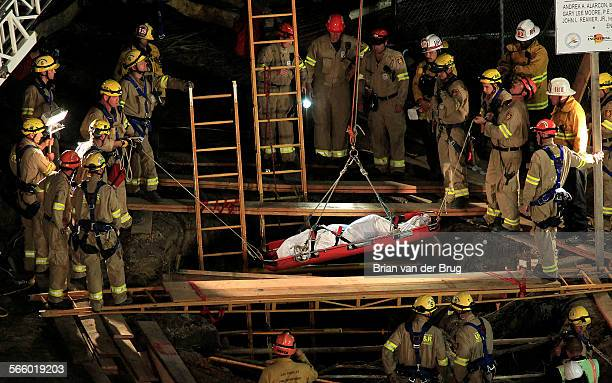 Firefighters remove the body of a worker who became trapped in a trench March 14 2013 in Pacific Palisades More than 50 firefighters were sent to the...