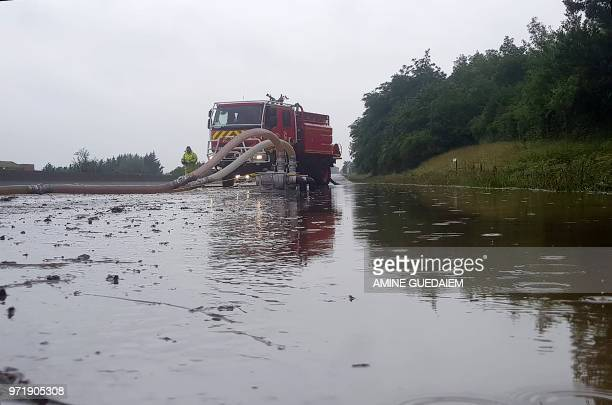 Firefighters remove water on the flooded A13 highway following heavy rains on June 12 2018 between Orgeval and VillennessurSeine