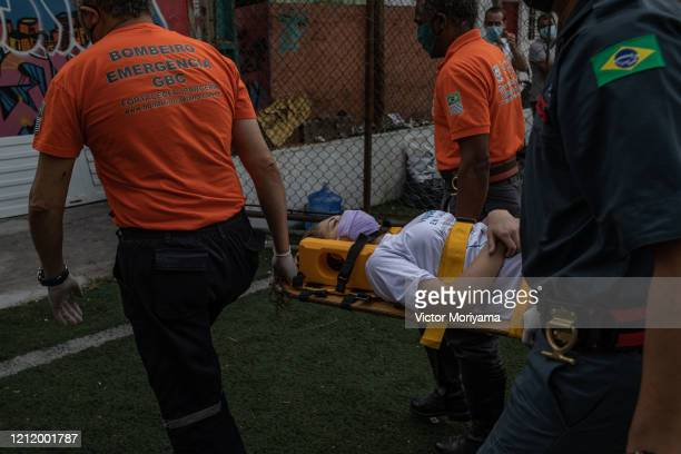 Firefighters rescue a woman who fell ill during first aid training in the Paraisopilis slum on May 6 2020 in Sao Paulo Brazil The local community...