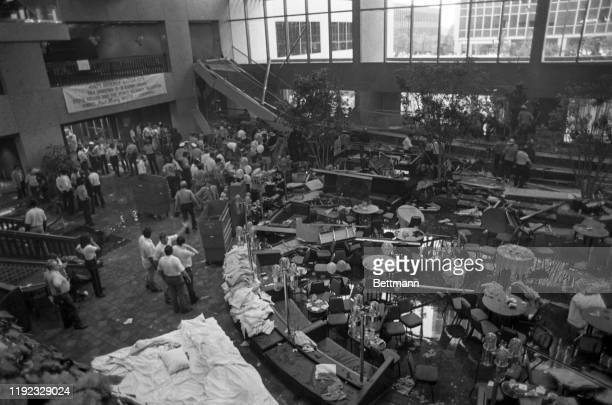 Firefighters rescue people from under a collapsed walkway in the lobby of the Hyatt Regency hotel. At least 25 people were killed and 100 injured by...