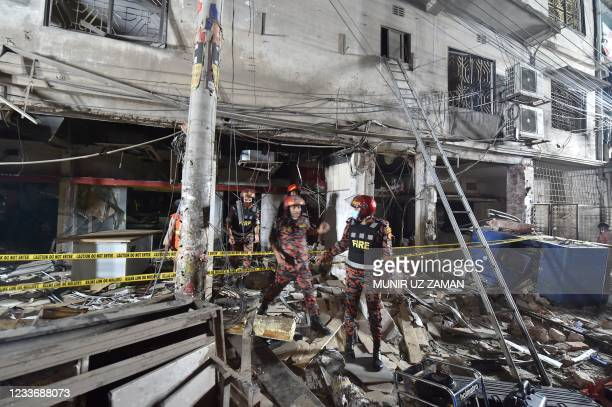 Firefighters rescuers inspect the scene after a suspected gas explosion in a central neighbourhood in the Bangladesh capital Dhaka which has killed...
