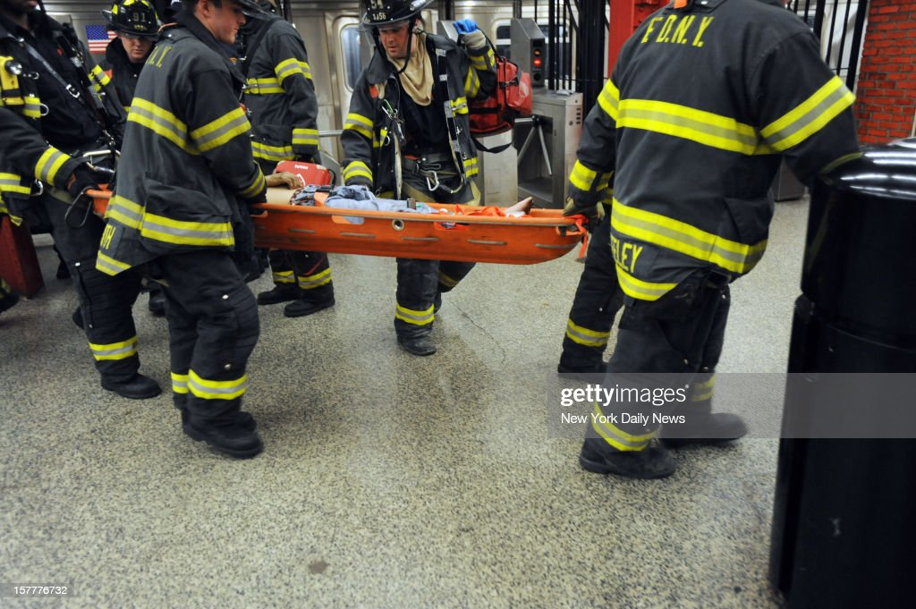 Firefighters rush Ki-Suk Han to hospital after the Queens man was hit by train at W. 49th St. station. The hunt is on for a madman who shoved this Queens father to his death in front of a subway train in midtown as stunned witnesses watched in horror. Han, 58, of Elmhurst, struggled to his feet after being pushed onto the tracks, and was desperately trying to get out of harm's way, when the downtown Q train slammed into him.