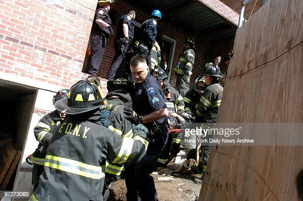 Firefighters rush victims to ambulances after a balcony collapsed and a day laborer fell to his death at a construction site in Bay Ridge Brooklyn...