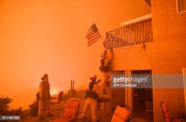 Firefighters save a US flag as impending flames from the Wall fire close in on a luxury home in Oroville, California on July 8, 2017. At least 10...