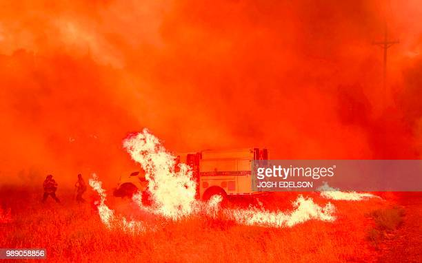 Firefighters scramble to control flames surrounding a fire truck as the Pawnee fire jumps across highway 20 near Clearlake Oaks California on July 01...