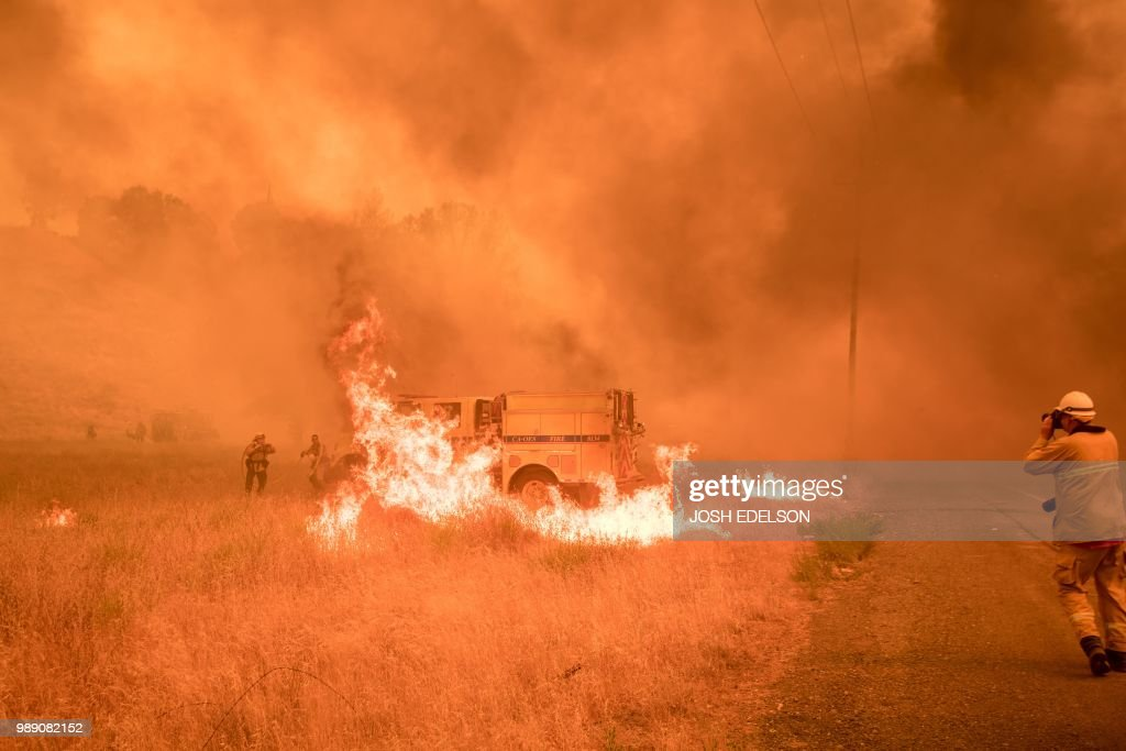 TOPSHOT - Firefighters scramble to control flames surrounding a fire truck as the Pawnee fire jumps across highway 20 near Clearlake Oaks, California on July 01, 2018. - More than 30,000 acres have burned in multiple fires throughout the region.