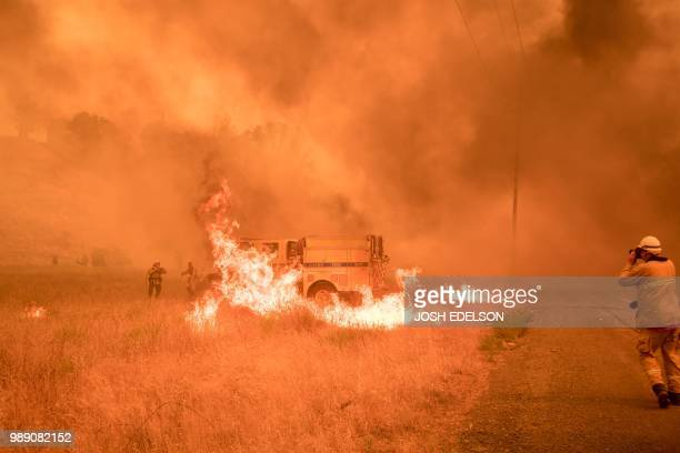TOPSHOT Firefighters scramble to control flames surrounding a fire truck as the Pawnee fire jumps across highway 20 near Clearlake Oaks California on...