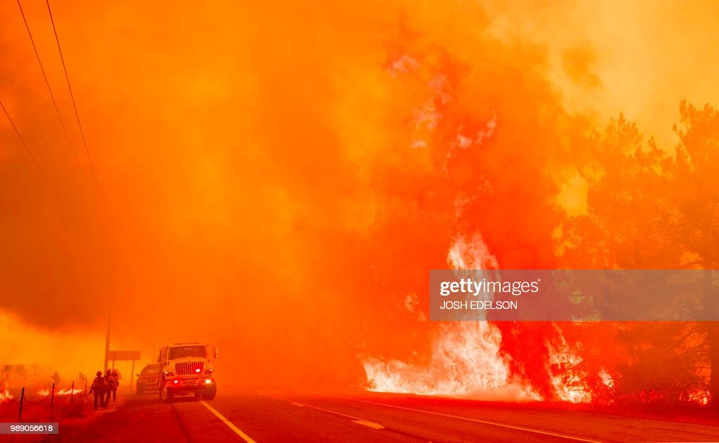 Firefighters scramble to get control as flames from the Pawnee fire jump across highway 20 near Clearlake Oaks, California on July 1, 2018. - More than 30,000 acres have burned in multiple fires throughout the region.