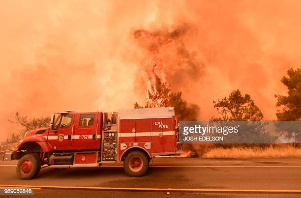 Firefighters scramble to get control as flames from the Pawnee fire jump across highway 20 near Clearlake Oaks California on July 1 2018 More than...
