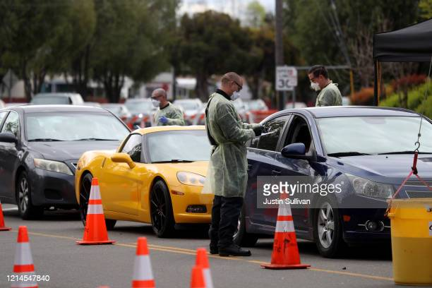 Firefighters screen people that are waiting in line to get a COVID19 test at a free public testing station on March 24 2020 in Hayward California...