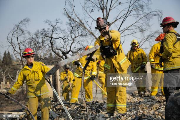 Firefighters search for a strongbox and a wedding ring through the remains of a home in the Fountaingrove neighborhood on October 13, 2017 in Santa...