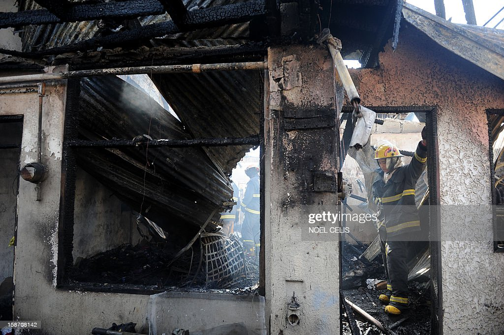 Firefighters search for bodies after a pre-dawn fire engulfed a row of old apartments in Manila on December 25, 2012. At least seven people were killed and thousands left homeless as two fires struck the Philippine capital on Christmas Day, sparking riots as a slum went up in flames, Manila's fire marshal said.