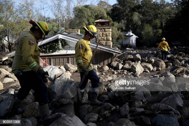 Firefighters search for people trapped in mudslide debris on January 10 2018 in Montecito California 15 people have died and hundreds are still...