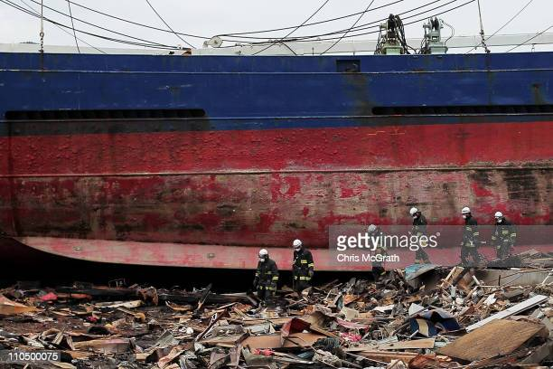 Firefighters search the rubble next to a large grounded cargo ship on March 21 2011 in Kesennuma Japan The 90 magnitude strong earthquake struck...