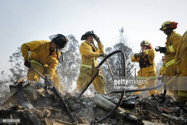 Firefighters search through the remains of a home in the Fountaingrove neighborhood for a strongbox and a wedding ring on October 13 2017 in Santa...