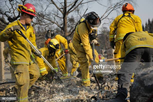 Firefighters search through the rubble of a home in the Fountaingrove neighborhood for a strongbox and a wedding ring on October 13 2017 in Santa...