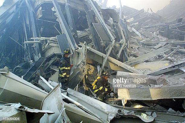 Firefighters search through the rubble of the twin towers at the World Trade Center in lower Manhattan 11 September in New York after two planes flew...