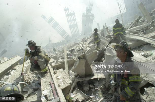 Firefighters search through the rubble of the World Trade Center after it was struck by a commercial airliner in a terrorist attack A hijacked...